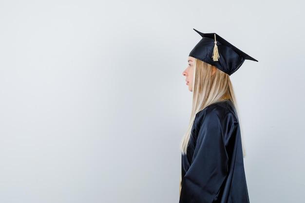 Jeune femme regardant loin en uniforme de diplômé et ayant l'air concentré. .