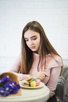Jeune femme regardant des macarons colorés sur le tableau blanc