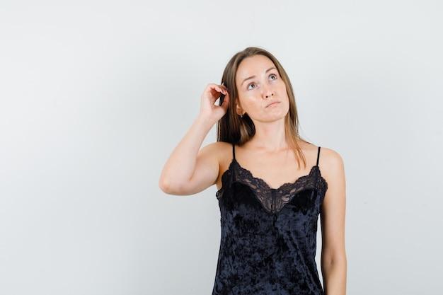 Jeune femme regardant avec la main sur les cheveux en maillot noir et à la réflexion