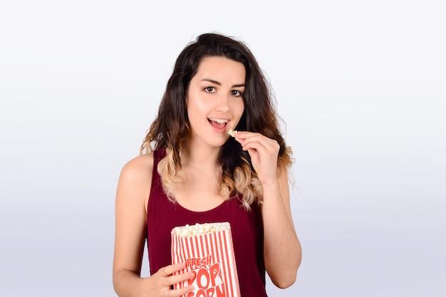 Jeune femme regardant manger du pop-corn.