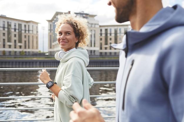 Jeune femme regardant son petit ami et souriant pendant leur jogging dans la ville