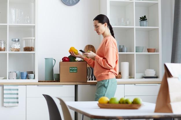 Jeune femme regardant son téléphone portable et vérifiant la nourriture dans la boîte en se tenant debout dans la cuisine