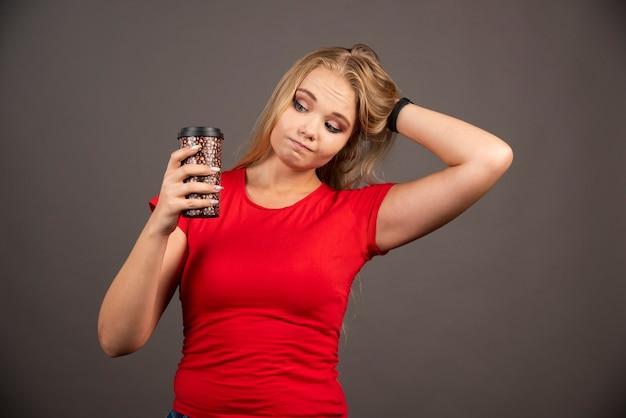 Jeune femme regardant une tasse de café sur un mur noir.