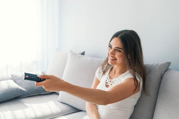 Jeune femme regardant la télévision dans la chambre