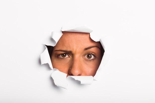 Jeune femme regardant à travers une déchirure de papier