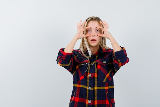 Jeune femme regardant à travers les doigts en chemise à carreaux et à la perplexité. vue de face.