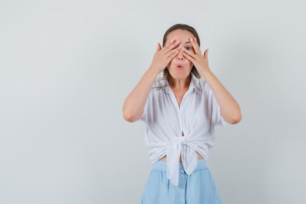 Jeune femme regardant à travers les doigts en chemisier, jupe et à la curiosité