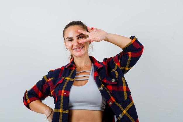 Jeune femme regardant à travers les doigts dans un haut court, une chemise à carreaux et une jolie vue de face.