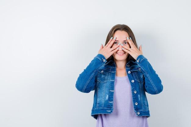 Jeune femme regardant à travers les doigts en t-shirt, veste et semblant joyeuse. vue de face.
