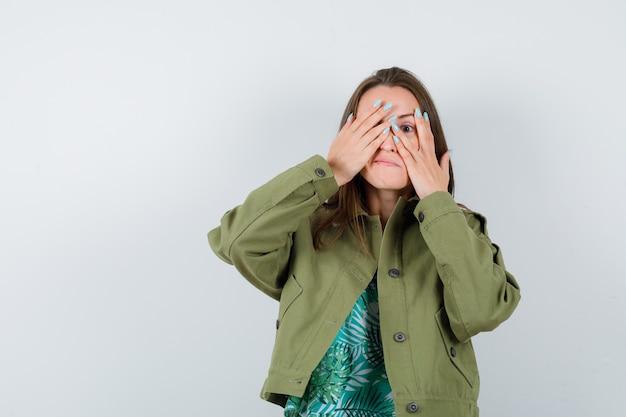 Jeune femme regardant à travers les doigts en veste verte et semblant curieuse, vue de face.