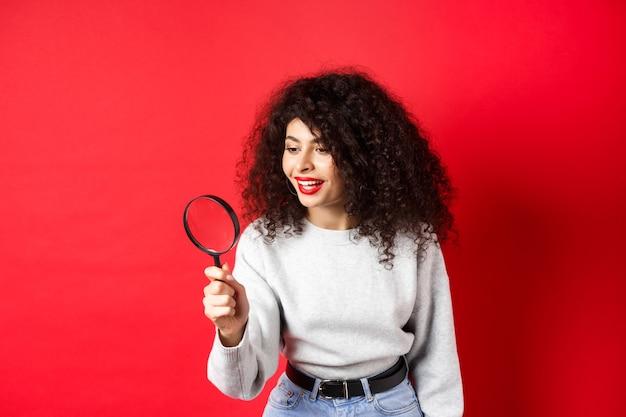 Jeune femme regardant à travers la loupe, enquêtant ou cherchant quelque chose, regard curieux de côté, a trouvé une chose intéressante, debout sur fond rouge.