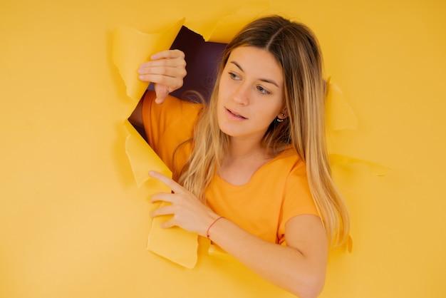 Jeune femme regardant à travers un trou déchiré dans le mur de papier.