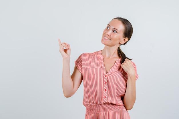 Jeune femme regardant vers le haut avec le doigt en robe rayée et à la joyeuse vue de face.