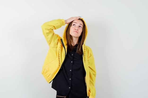Jeune femme regardant vers le haut avec la main sur la tête