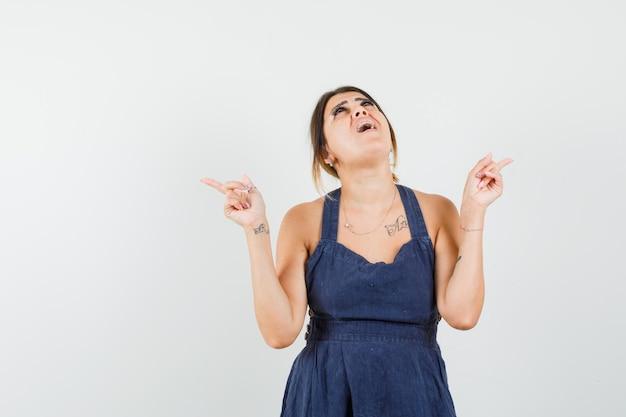 Jeune femme regardant vers le haut, pointant vers l'extérieur en robe et l'air étonné