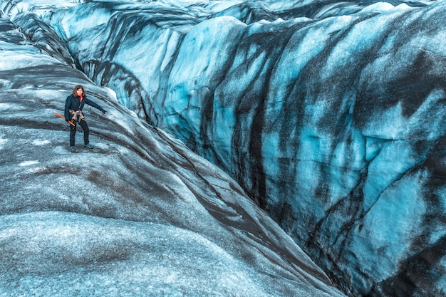 Une jeune femme regarde l'un des dangereux trous de randonnée sur glace dans le glacier svinafellsjokull. islande