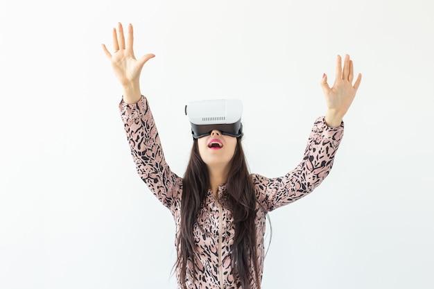 Jeune femme regarde un film avec des lunettes de réalité virtuelle debout sur une surface blanche. le