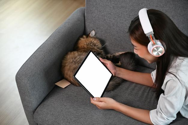 Une jeune femme regarde un film sur une tablette avec écran vide en position couchée sur le canapé.