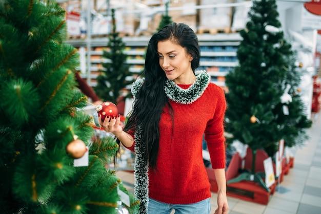 Jeune femme regarde le jouet d'arbre de noël dans un supermarché.