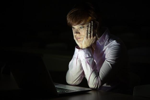 Jeune, femme, regarde, ordinateur portable, sombre, salle