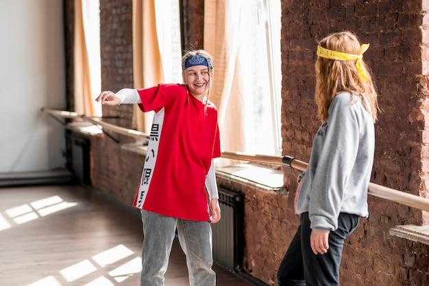 Jeune femme regarde sa copine danser dans la classe