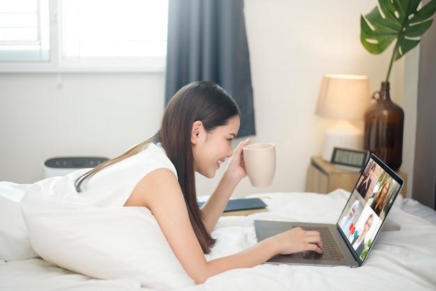 Jeune femme regarde son écran d'ordinateur lors d'une réunion d'affaires via une application de vidéoconférence