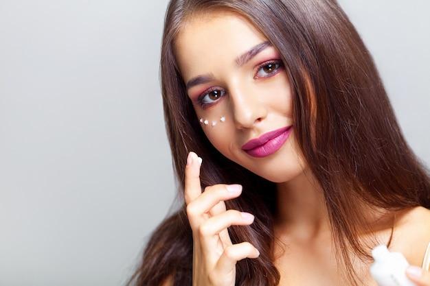 Jeune femme, regarder appareil-photo, à, hydratant visage, près, yeux