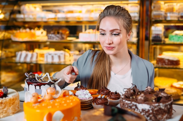 Jeune, femme, regarder, boulangerie, fenêtre, différent, morceaux, gâteaux