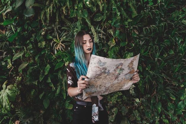 Jeune femme, regarder, carte vintage, debout, devant, plante
