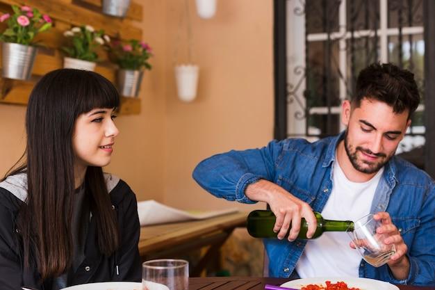 Jeune femme, regarder, homme, verser, alcool, dans, verre