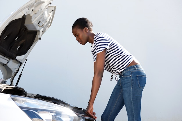Jeune femme, regarder, sous, les, capot, de, voiture cassée, sur, route