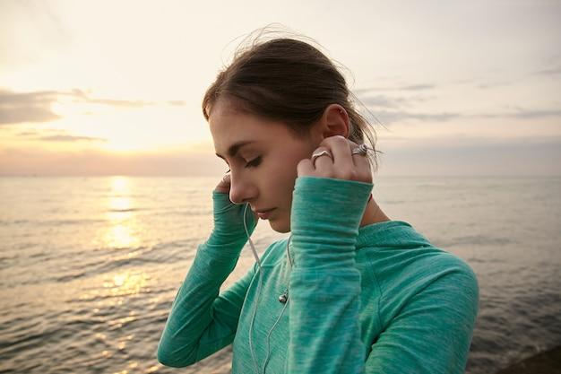 Jeune femme relaxante au bord de la mer au coucher du soleil, écoutant la musique préférée au casque.