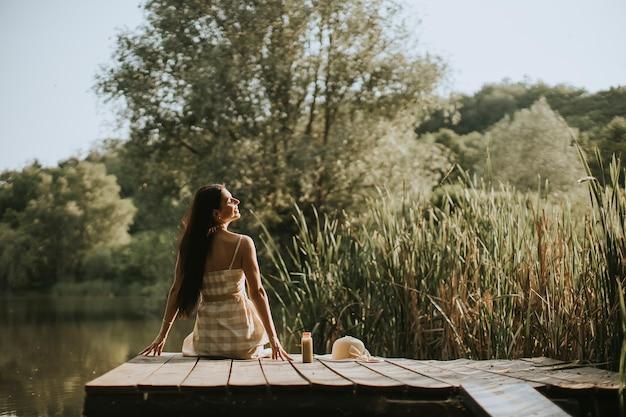 Jeune femme relaxante sur une jetée en bois au bord du lac calme