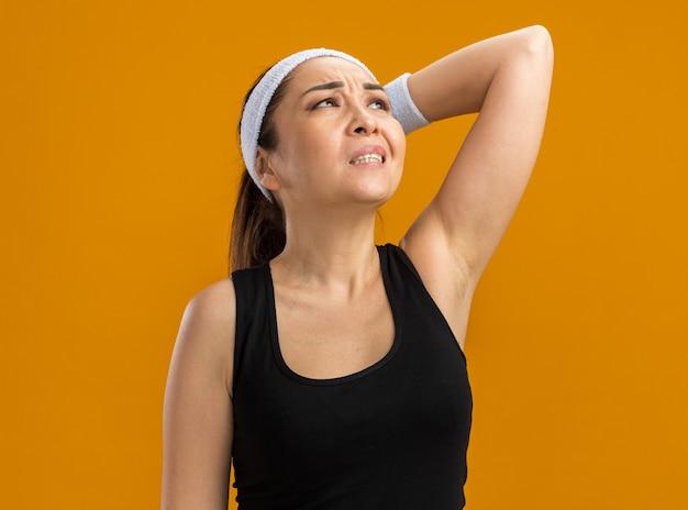 Jeune femme de remise en forme avec bandeau et brassards levant confus étant fatigué debout sur le mur orange