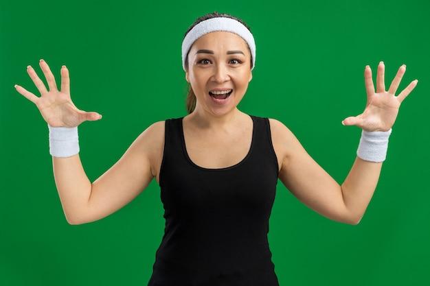 Jeune femme de remise en forme avec bandeau et brassards souriant heureux et excité avec les bras levés