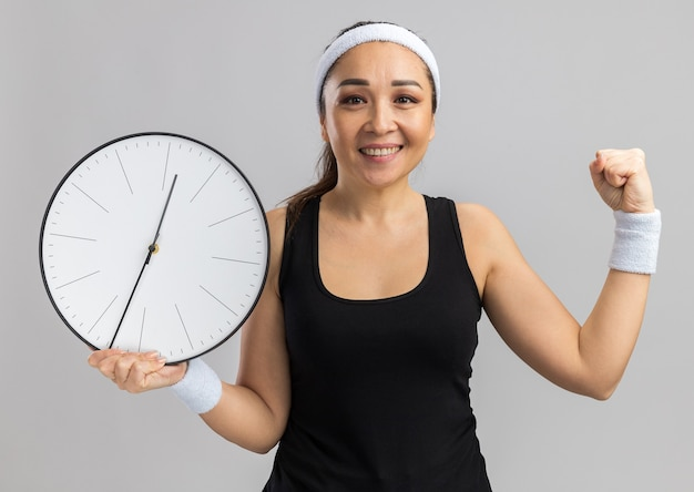 Jeune femme de remise en forme avec bandeau et brassards tenant une horloge murale avec un sourire sur le visage serrant le poing debout sur un mur blanc