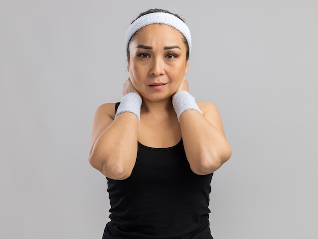 Jeune femme de remise en forme avec bandeau et brassards avec un visage sérieux touchant son cou debout sur un mur blanc