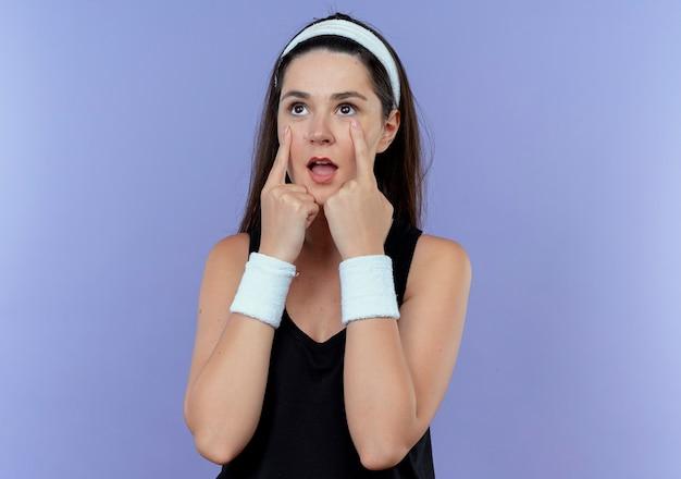 Jeune femme de remise en forme en bandeau à côté en pointant avec les doigts à ses yeux debout sur fond bleu