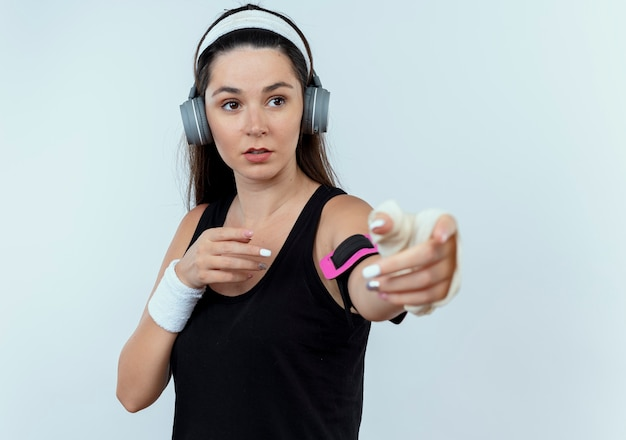 Jeune femme de remise en forme en bandeau avec des écouteurs et brassard de smartphone à la recherche de côté avec les bras debout sur fond blanc