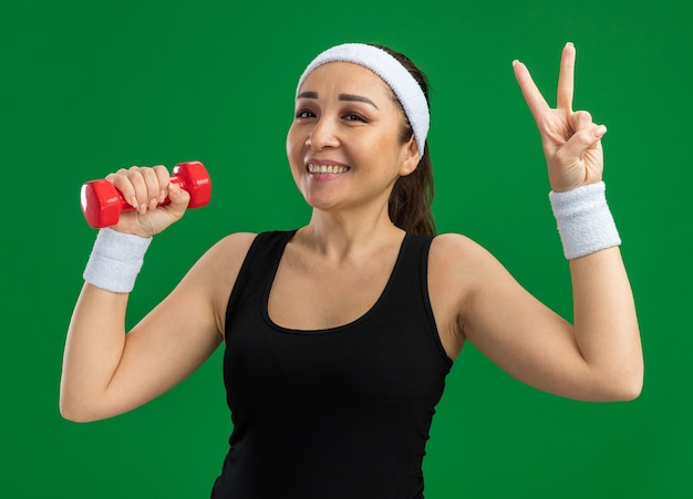 Jeune femme de remise en forme avec bandeau avec haltère faisant des exercices souriant montrant le signe v debout sur un mur vert