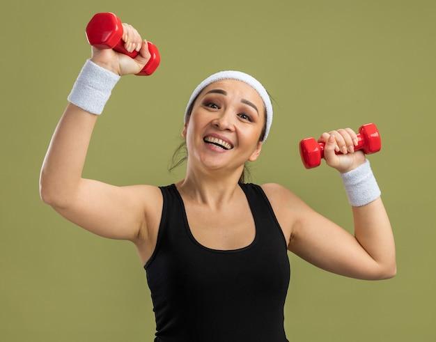 Jeune femme de remise en forme avec bandeau avec haltères faisant des exercices heureux et excité debout sur un mur vert