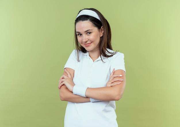 Jeune femme de remise en forme en bandeau regardant la caméra avec une expression confiante avec les bras croisés souriant debout sur fond clair