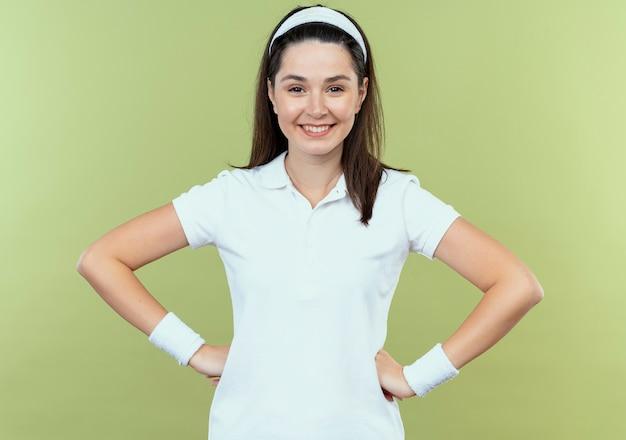Jeune femme de remise en forme en bandeau regardant la caméra en souriant joyeusement heureux et positif debout sur fond clair