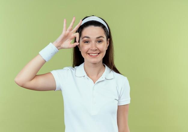 Jeune femme de remise en forme en bandeau regardant la caméra en souriant joyeusement montrant signe ok debout sur fond clair