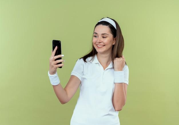 Jeune femme de remise en forme en bandeau regardant l'écran de son smartphone serrant le poing heureux et excité debout sur un mur léger