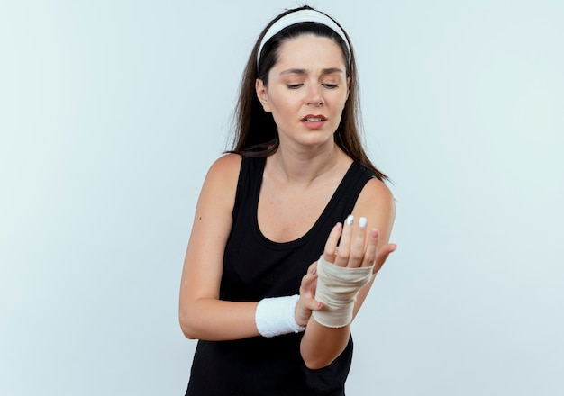 Jeune femme de remise en forme en bandeau en regardant son poignet bandé sensation de douleur debout sur fond blanc