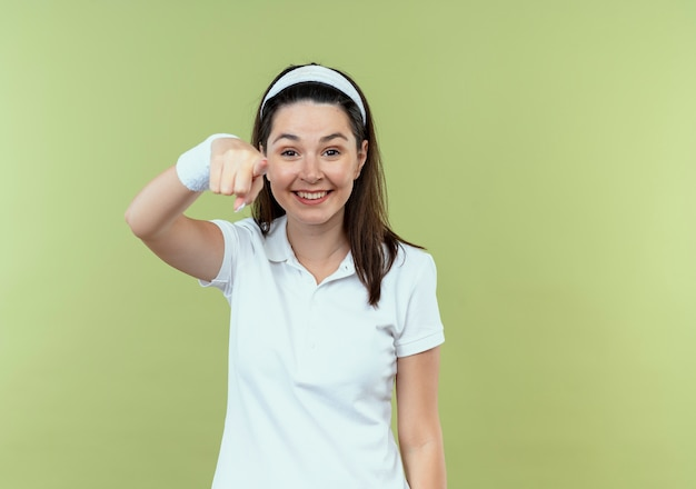Jeune femme de remise en forme en bandeau souriant joyeusement pointant avec le doigt à la caméra debout sur fond clair