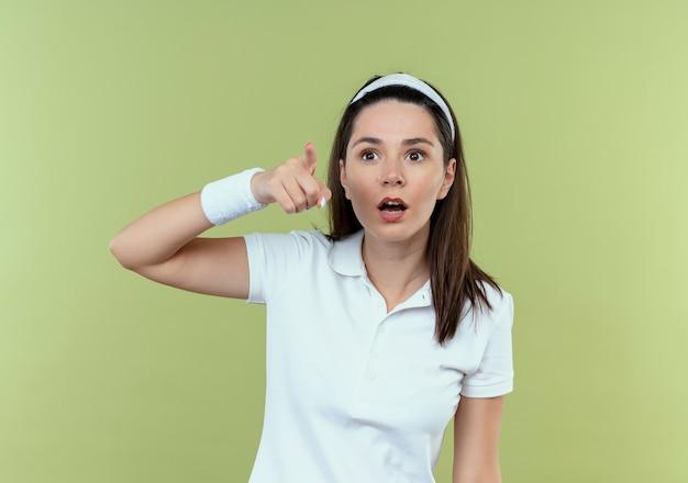Jeune femme de remise en forme en bandeau à la surprise de pointer du doigt quelque chose debout sur fond clair