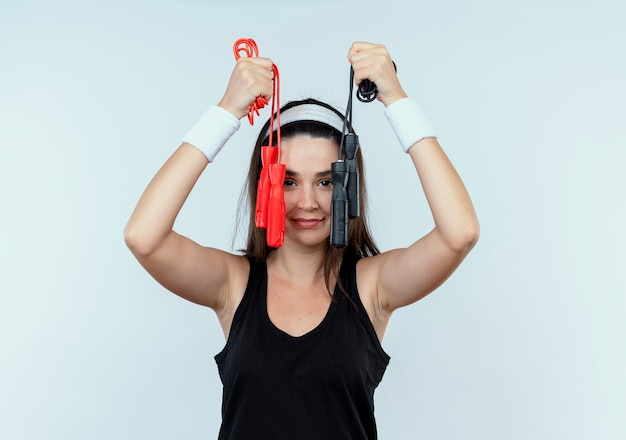 Jeune femme de remise en forme en bandeau tenant la corde à sauter avec le sourire sur le visage debout sur un mur blanc