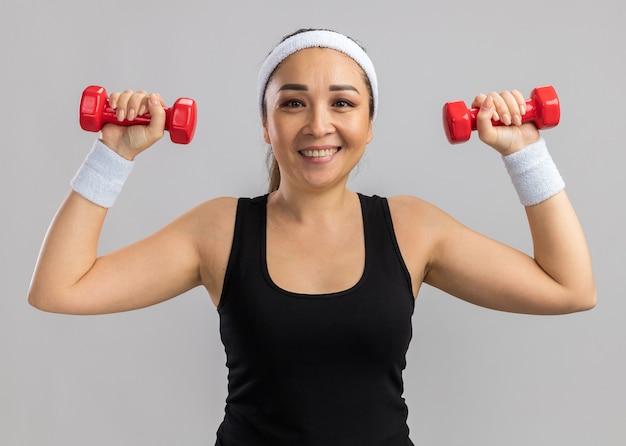 Jeune femme de remise en forme avec bandeau tenant des haltères faisant des exercices à l'air confiant souriant debout sur un mur blanc